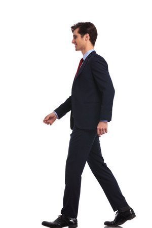 vue de côté d'un jeune homme d'affaires marchant, isolé sur fond blanc