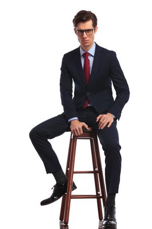 seria del hombre de negocios joven que llevaba gafas está sentado en una silla y mira ath la cámara, foto de cuerpo entero aisladas sobre fondo blanco Foto de archivo