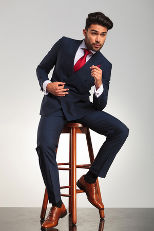 side view picture of a young business man in elegant modern suit sitting on a stool and looks away from the camera Stock Photo
