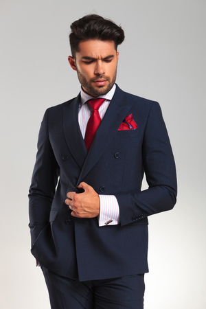 double breasted: arrogant young business man looking to side while holding a button on his suit on grey background Stock Photo