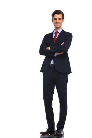 手が白いスタジオ背景に交差の側に立って成功する若いビジネス人