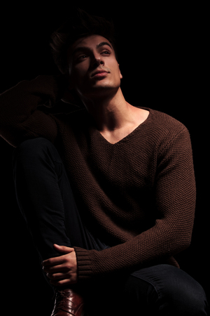 resting: seated handsome man dreaming away on black studio background