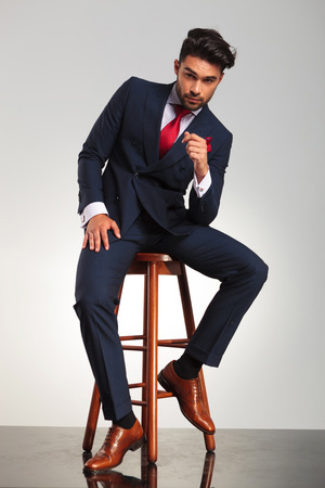 serious business man in elegant double breasted suit sitting on a chair on grey studio background Stock Photo
