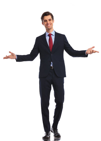 white suit: smiling young business man in suit and tie welcoming you on white studio background Stock Photo