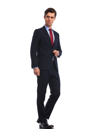 casual business man: side view of a young business man standing and looks away from the camera on white background