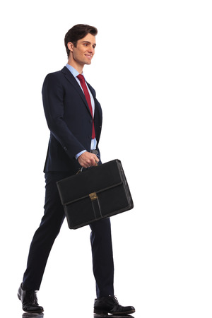 bakground: young man in suit and tie laughing while walking with briefcase on white bakground Stock Photo