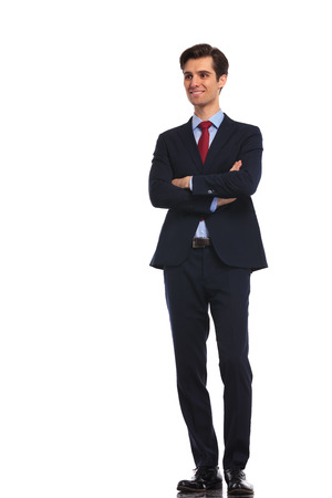 folded hands: smiling young business man in suit and tie dreaming at something on white studio background