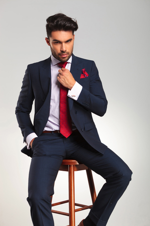 double breasted: seated elegant business man fixing his tie on grey studio background Stock Photo