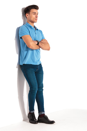 mani incrociate: full body picture of a young casual man in blue polo shirt, leaning against studio wall with hands crossed and looking away from the camera Archivio Fotografico