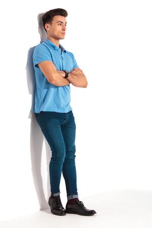 mani incrociate: quadro completo del corpo di un giovane uomo casual in camicia polo blu, appoggiata contro il muro in studio con le mani incrociate e guardando lontano dalla fotocamera
