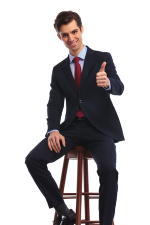 seated young business man making the ok thumbs up hand sign on white background