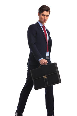 serious businessman in suit and tie holding a briefcase is walking and looks at the camera on white background