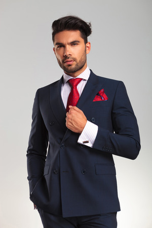 double breasted: elegant business man in double breasted suit looking up and thinking on grey studio background