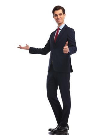 full body foto van een jonge zakenman presenteren en het maken van de ok duimen omhoog hand ondertekenen, geïsoleerd op een witte achtergrond Stockfoto