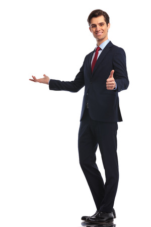 full body picture of a  young business man presenting and making the ok thumbs up hand sign, isolated on white background Archivio Fotografico