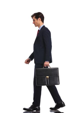 full body foto van een jonge business man lopen vooruit en met een aktetas, geïsoleerd op een witte achtergrond