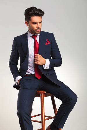 double breasted: side view of an elegant business man holding his coat and looks away from the camera while sitting on a stool