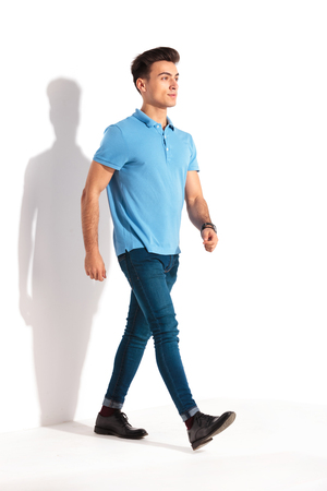 confident young casual man in polo shirt and jeans walking forward in studio Stock Photo