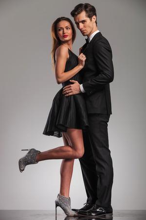 vista lateral de la elegante pareja abrazada en la ropa negra, mujer mirando hacia atrás mientras mantiene su amante Foto de archivo