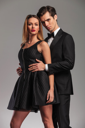 elegant couple in studio, man embacing his woman from behind, holding hands on her waist Imagens