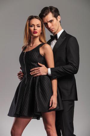 elegante pareja en el estudio, el hombre embacing su mujer por detrás, de la mano en la cintura