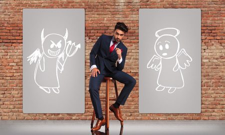 double breasted: young business man in double breasted suit making a decision between good or bad