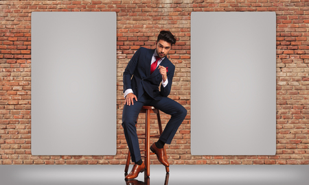 double breasted: elegant man in double breasted suit sitting near two blank billboards and thinking