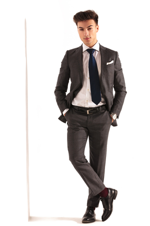 man legs: sexy young business man with hands in pockets standing near wall in studio
