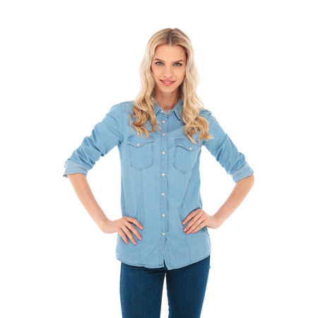 smiling blonde woman standing with hands on waist on white background