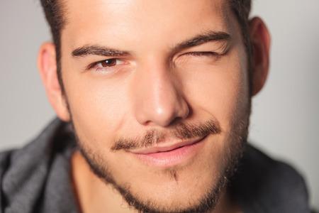 smilling 若い男がスタジオで彼の目は、クローズ アップ写真がきらめいてください。