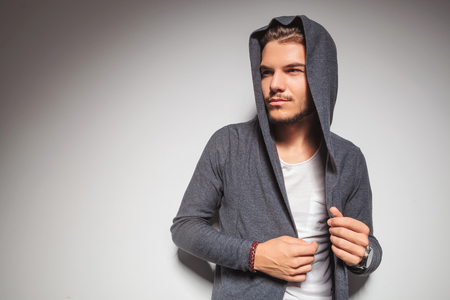 young male: young casual man with hoodie on looking to side on grey studio background