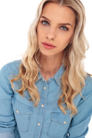 blue shirt: young fashion blond woman posing for the camera in studio Stock Photo
