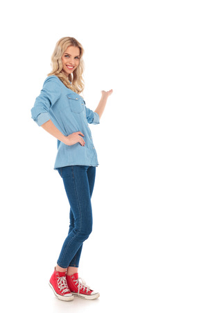 presenting: full body picture of a smiling young casual woman presenting something on white background Stock Photo