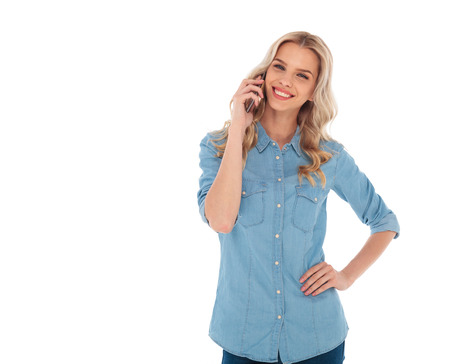 happy smiling blonde casual woman talking on the phone on white background Foto de archivo