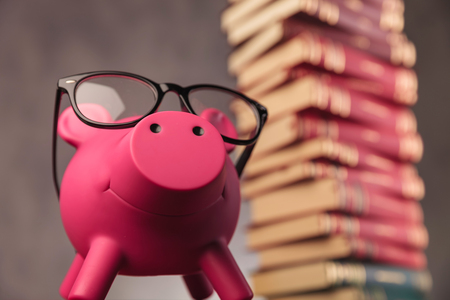 happy piggy bank wearing glasses looks up while standing near a big pile of books