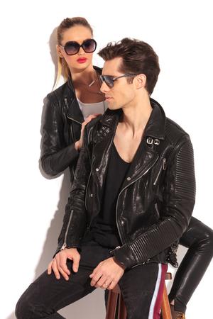 hombre sentado: Mujer en la chaqueta de cuero está buscando a su hombre sentado, tanto el desgaste gafas de sol en estudio Foto de archivo