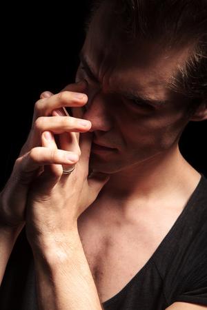 hombre orando: dramatic young man praying in studio, on black background Foto de archivo