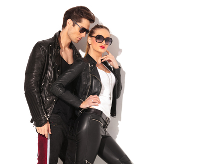 hot pants: sexy woman in leather clothes standing near boyfriend with finger on her chin in studio