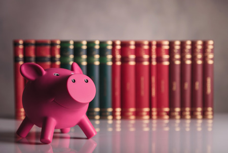 smart investing: pink piggy bank in front of a row of books - studio picture