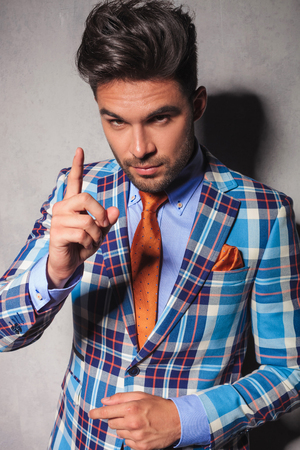 behave: elegant man in checkered suit gesturing for you to behave or to have your attention
