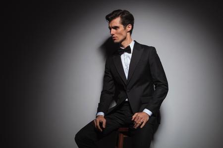 seated man: vista lateral de un hombre sentado vistiendo esmoquin y pajarita, estudio de imagen con copyspace