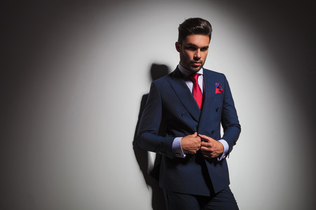 double breasted: confident businessman buttoning his suit and looks at the camera, leaning on a grey studio wall Stock Photo