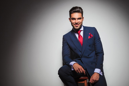 double breasted: happy young businessman in elegant suit resting on a chair in studio