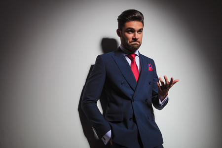 double breasted: confused elegant man gesturing and making an undecided stupid face, leaning on a grey studio wall Stock Photo