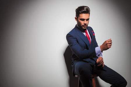 double breasted: seated young business man in double breasted suit is gesturing while looking down at something in studio Stock Photo