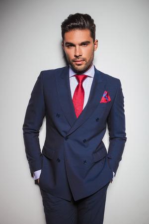 uomo rosso: Ritratto di un uomo rilassato elegante in doppio petto abito in piedi con le mani in tasche in studio