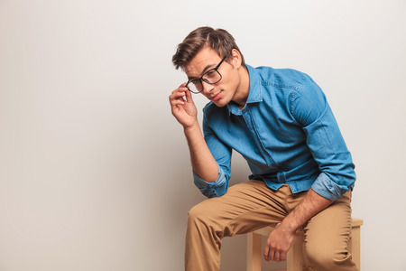 seated man: young casual seated man is taking off his glasses , side view picture on grey background Foto de archivo