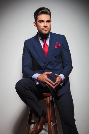 double breasted: seated young elegant man in suit and tie looking away to side , studio picture Stock Photo