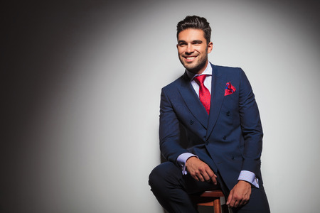 double breasted: side view of a smiling gentleman sitting on a chair in studio and looks to side Stock Photo