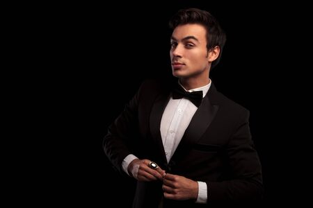 cool elegant young man in tuxedo unbuttoning his coat on black studio background Stock Photo